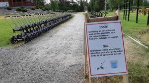 En rad golfkärror och en skylt där golfare uppmanas desinfiera golfkärran.