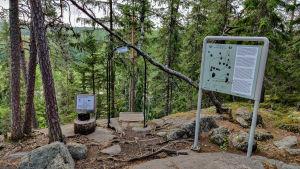 En informationsskylt på ett berg i skogen.