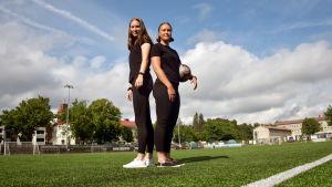 Felicia Gröning och Jill Illman står rygg mot rygg på en konstgräsplan. Jill håller i en fotboll.