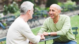 Två medelålders män sitter på uteservering, håller varandra i handen och ler