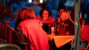 Ett gäng kvinnor sitter på en uteservering på kvällen och dricker en och samma stora dryck ur sugrör. Det lyser ett rött sken på kvinnorna.