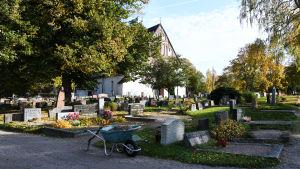 Begravningsplats med gammal stenkyrka i bakgrunden. Längst fram står en skottkärra.