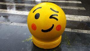 Emojin näköiseksi maalattu liikennehidaste suojatien vieressä