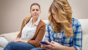 Misstänksam mamma tittar på tonårsdotter som tittar på sin telefon.