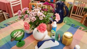 Blommor i vas på bord med kaffekoppar och termos.