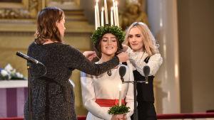 Li Andersson och Jannike Sandström trär ett halsband runt lucia Ingrid Enckell.