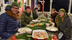 Några personer som sitter utomhus och äter en middag på en veranda på vintern. Bordet är juldukat.