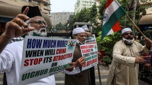 En grupp män står med plakat som fördömer Kinas förföljelser av uigurerna.