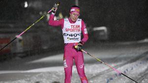 Kerttu Niskanen sträcker armen uppåt då hon åker över mållinjen.