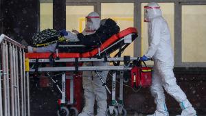 Två sjukvårdare klädda i vit skyddsutrustning skuffar en person på en orange bår.