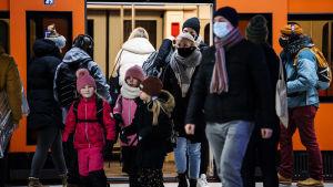 Personer i munskydd stiger av metron.