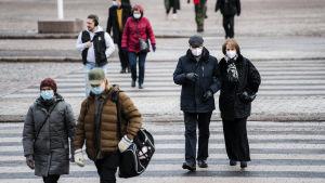 Människor i munskydd går i Helsingfors centrum i februari 2021.