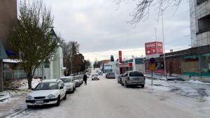 En snöbeklädd väg. På sidorna syns parkerade bilar och till höger syns en butik.