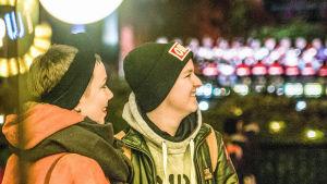 Olivia och Emil står tätt ihop och tittar bort från kameran. I bakgrunden syns en massa lysande lampor.