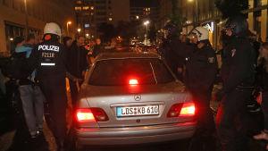 Tyska poliser skyddar en AfD-politikers bil från demonstranter.