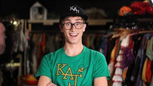 Christoffer Strandberg utklädd till medlemmarna i humorgruppen KAJ. Han bär svart keps och grön t-skjorta som det står KAJ på.