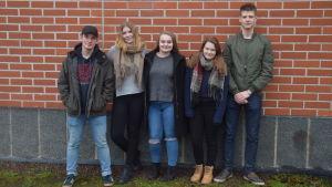 Ungdomar står mot en tegelvägg.