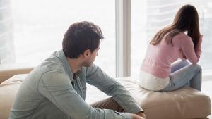 Man och kvinna sitter på säng, kvinnan vänder sig bort från mannen