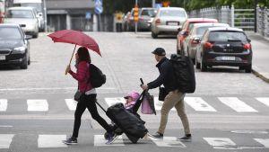 En kvinna med paraply och en man med barnvagn går över ett övergångsställe i stadsmiljö på midsommaren 2017.