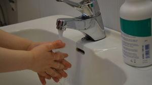 Ett barn tvättar sina händer i ett tvättställ.