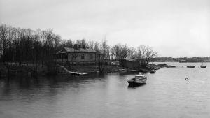 En roddbåt ligger förtöjd vid en villa på Busholmen, fotat år 1913.