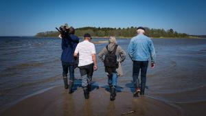 människor går mot en holme i grunt vatten