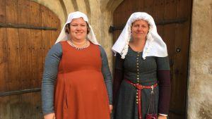 två kvinnor är utklädda i medeltidsdräkter.