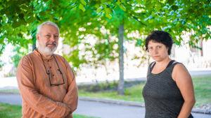 En man och en kvinna står och tittar allvarsamt in i kameran. I bakgrunden syns träd, många gröna löv.