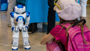 Lapsi katselee Nao-robottia, jota ohjataan tekoälyn avulla.