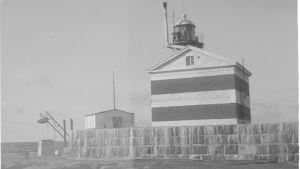 Mustavalkoinen kuva: Raidallisen majakan pääty, ympärillä muuri. Vierellä pienempi varastorakennus.