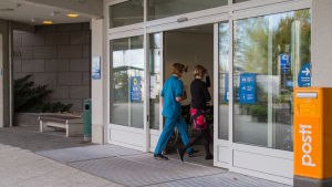 En sjukskötare och patient går in genom sjukhusdörrar