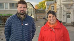 en man i blå dunrock och en kvinna i röd jacka står ute på Rådhustorget i Ekenäs. De ser mot kameran och ler.