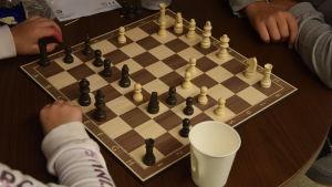 Ett schackbräde och två barn som spelar. Man ser bara händerna på barnen.