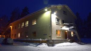 En beige skolbyggnad omringad av snö. På väggen står det Svartå skola.