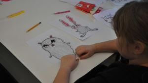 Ett barn målar på en figur på ett papper.