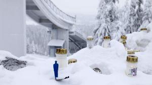 Gravljus och en liten, blå backhopparfigur i plast vid hoppbacken i Jyväskylä, till minne av Matti Nykänen.