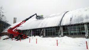 Snö röjs bort av taket på Vasa simhall.