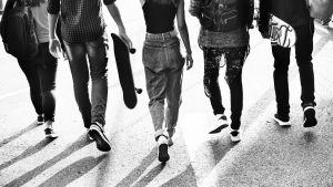 Svartvit bild på ett gäng tonåringar som promenerar bredvid varandra.