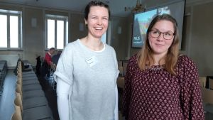 Två unga kvinnor i skolsal med stolar och bioduk längst fram. En ena kvinnarn ler stort och den andra ser underfundig ut. Den ena är klädd i ljusa kläder och den andra i mörkt