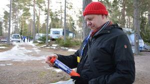 Kenneth Sandholm, en man med röd mössa, läser anvisningarna för hur man ska använda den nödraket han har i handen.