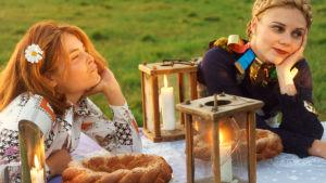 Irina Björklund ja Usva Kärnä kesäisen pöydän ääressä ulkona. Kuva elokuvasta Ruusutarha.
