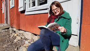 En kvinna sitter på en trappa och läser en bok.