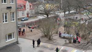 Barn och vuxna på skolgård.