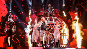 Islands representant Hatari med artister i läderkläder och i bakgrunden en pyroshow  under eurovisionen 2019.