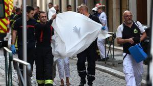 Nödarbetare bär en person som skadats i en explosion i centrala Lyon i Frankrike.