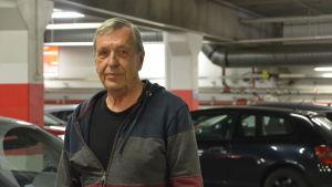 man står vid sin bil i en parkeringsgrotta.