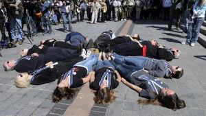 På marken, omgiven av en folkmassa, ligger tretton personer, placerade i en ring. De representerar de personer som dog i Colubinemassakern.