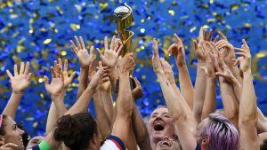 USA:s damfotbollspelare håller i en pokal och jublar.
