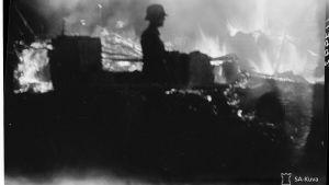 En soldat står vid ett brinnande förråd.