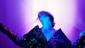 Skådespelaren Sue Lemström poserar med armarna utsträckta och huvudet bakåtlutat mot en neonviolett bakgrund.
